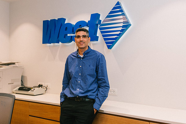 West Employee in front of the West Logo Sign