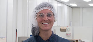 Gowned Employee smiling into the camera