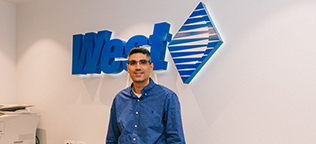 West Employee standing in front of the West logo sign